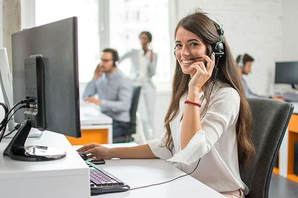 female customer service representative smiling on the phone